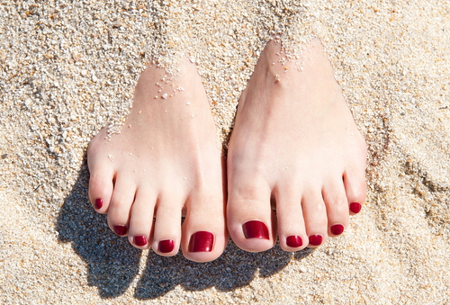 female-feet-with-red-pedicure-in-beach-sand1